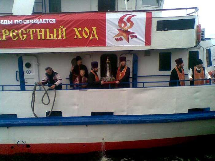 Preotii ortodocsi cu asa-zisa mana a Sf. Gheorghe si cu un banner pe care se afla o stea inversata si numarul 65 (pentru victorie)